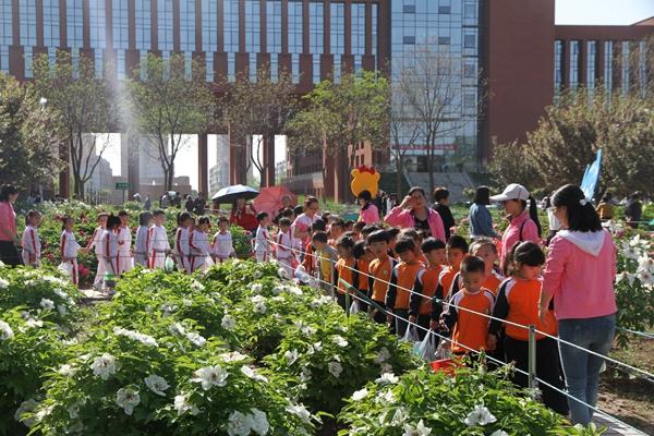 """四月的农林科大绿草如茵、花团锦簇。美丽的大学校园里,110万平方米的绿地,28000余株灌木,2.3万平方米苗圃,成了孩子们天然的户外活动场地。4月15日、17日,幼儿园组织开展了一场以""""约会春天""""为主题的春游活动。全体教师、幼儿及家长共计2000人参加了活动。   在农科大楼前,分院园区组织小班幼儿和家长以共跳亲子操的形式走入春天,在节奏欢快的音乐声中,家长们见证孩子们快乐的成长时光。""""吹泡泡""""、""""泡泡堂""""等亲子游戏增进了家长和"""